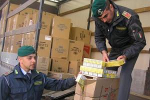 I militari del comando provinciale della Guardia di Finanza di Napoli controllano uno scatolone del tir con il carico di 4 tonnellate di sigarette sequestrato allo svincolo autostradale di Pagani-Nocera, nel Salernitano,  23 novembre 2011. ANSA/UFFICIO STAMPA GUARDIA DI FINANZA DI NAPOLI   +++NO SALES - EDITORIAL USE ONLY+++