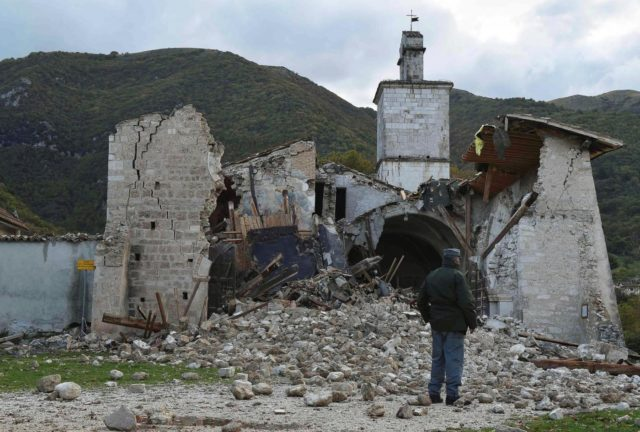 An officer of the State Forestry Corp national police stands in front of a collapsed church in Campi di Norcia, central Italy, October 27, 2016. REUTERS/Emiliano Grillotti   FOR EDITORIAL USE ONLY. NO RESALES. NO ARCHIVES.