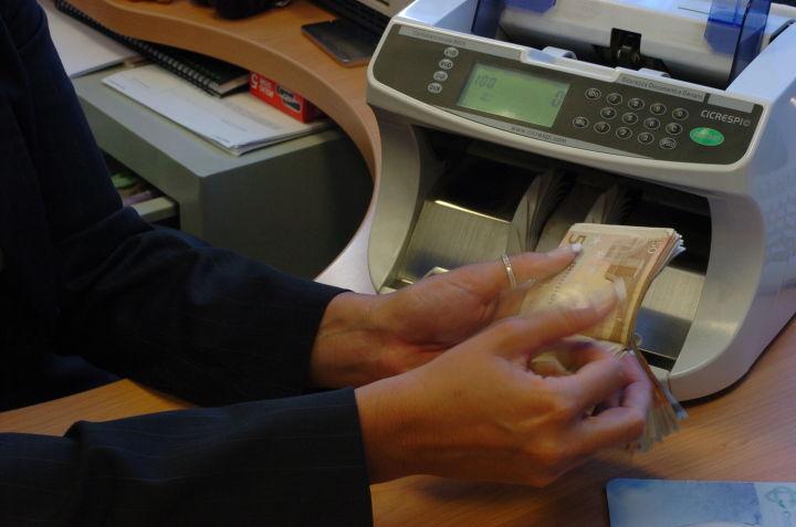 Una donna conta alcune banconote in uno sportello bancario, in una immagine di archivio. Piu' prestiti bancari alle famiglie italiane, soprattutto al Sud mentre calano quelli alle imprese: a marzo 2010 rispetto ad un anno prima - spiega Bankitalia nel volume 'L'andamento del credito nelle regioni italiane nel primo trimestre del 2010' - i prestiti alle famiglie consumatrici sono aumentati del 4,2% sui 12 mesi, in accelerazione rispetto al dato di dicembre. ANSA/MARIO DE RENZIS/DRN