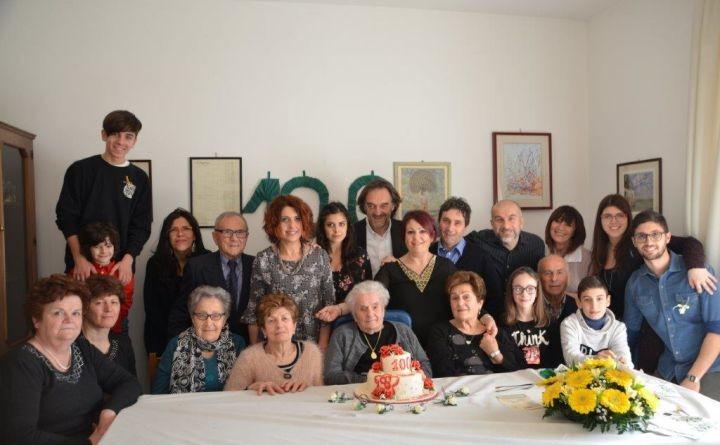 PILA nonna Clara dietro la torta circondata dai parenti